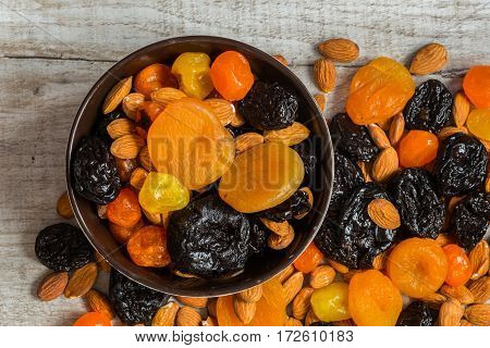 prunes, dried apricots, dried mandarins and almonds in a bowl on a light wooden background.