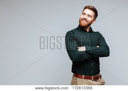 Smiling Bearded man in green shirt with crossed arms which looking away