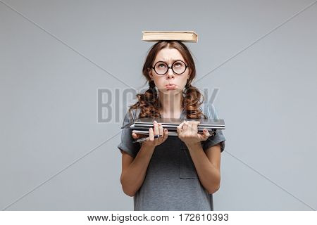 Upset Female nerd in funny eyeglasses with book on head which holding laptop and notebook in hand