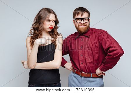 Displeased woman which pointing on funny male nerd