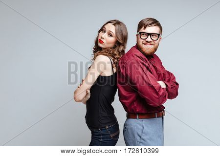 Pretty woman and Male nerd standing backs to each other. Isolated gray background