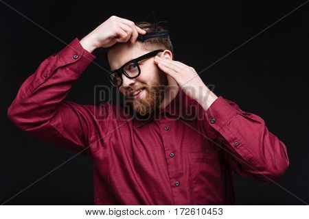 Smiling Male nerd combing his hair and looking at camera