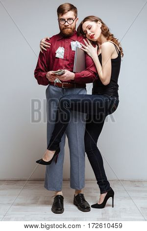 Vertical image of Woman stick to the Male nerd with money