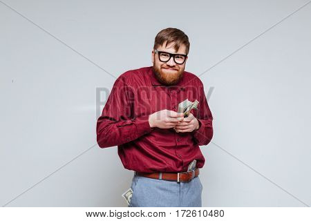 Funny male nerd in eyeglasses with money in hand. Isolated gray background