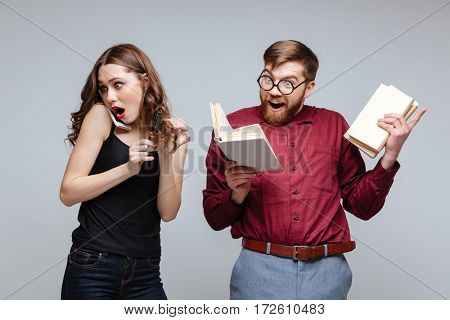 Woman talking on phone near the male nerd while he reading book