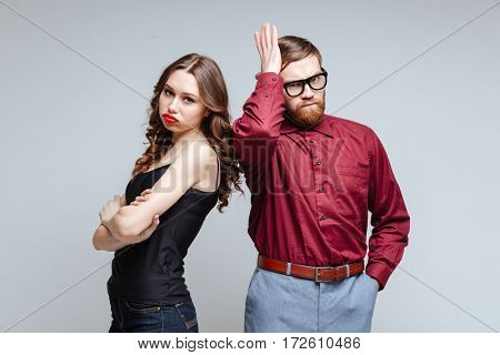 Displeased woman with male nerd in funny clothes and eyeglasses