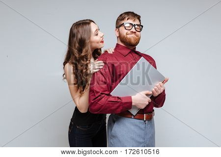 Woman from back of Male nerd in eyeglasses which holding the laptop