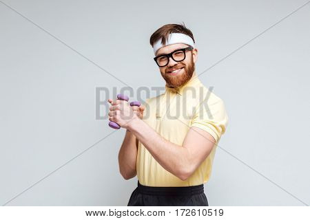 Funny male nerd in eyeglasses with dumbbells. Isolated gray background