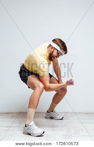 Vertical image of male nerd training with light dumbbells. Isolated gray background