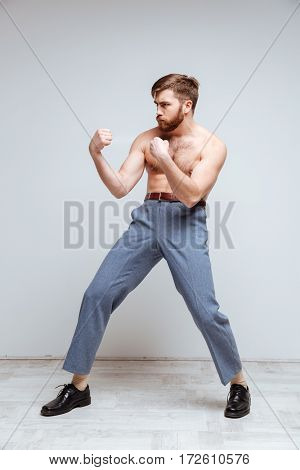 Vertical image of Serious Male nerd as fighter with naked torso