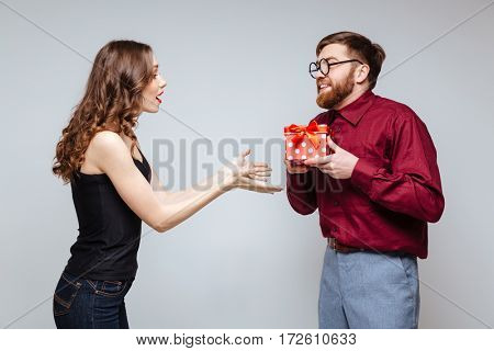 Male nerd presents the gift for Woman. Isolated gray background
