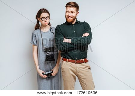 Female nerd in eyeglasses and retro camera on the neck with smiling beard man