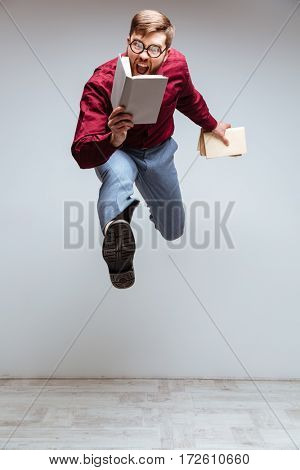 Vertical image of Male nerd jumping in studio with books in hands