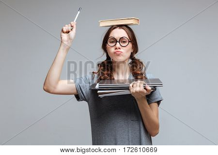 Young Female nerd in funny eyeglasses with book on head which holding laptop and notebook in hand