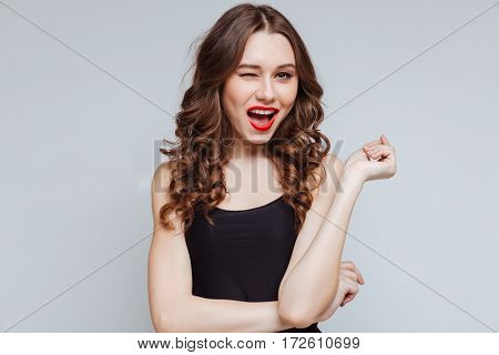 Happy woman which winks. Isolated gray background