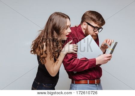 Young Woman standing from back of Male nerd which recounts the money and holding laptop