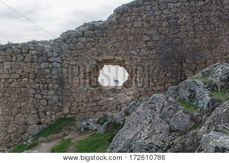 White old windmill on the hill near Consuegra (Castilla La Mancha Spain) a symbol of region and journeys of Don Quixote (Alonso Quijano) and a town on cloudy day a view through a hole in the wall.