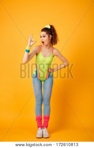 Photo of happy young fitness woman posing over yellow background. Looking at camera make okay gesture.