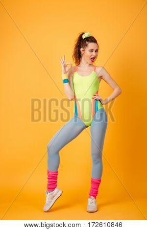 Picture of smiling young fitness lady posing over yellow background. Looking at camera make okay gesture.