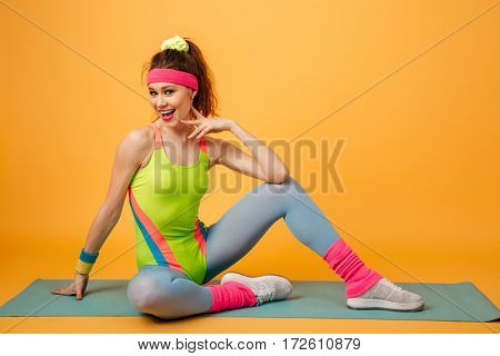 Image of incredible young sports lady make sports exercises over yellow background. Looking at camera.