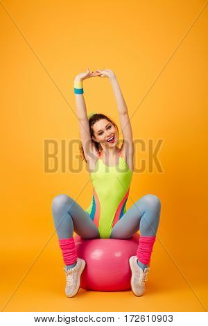 Image of amazing young fitness woman posing over yellow background. Looking at camera.