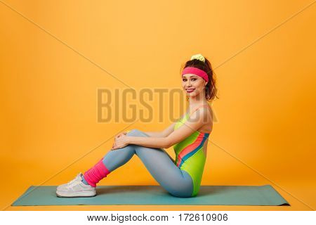 Photo of attractive young sports lady make sports exercises over yellow background. Looking at camera.
