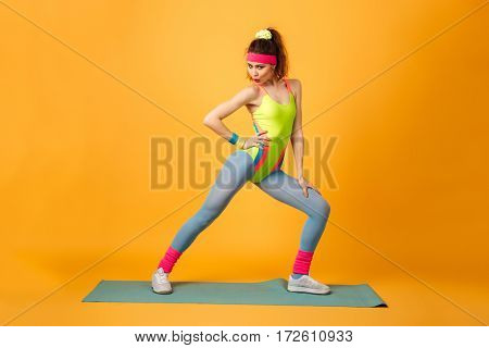Photo of pretty young sports lady make sports exercises over yellow background. Looking at camera.