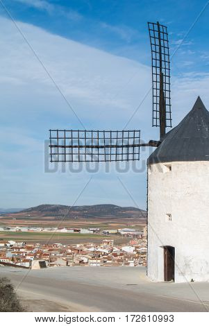 White old windmill on the hill near Consuegra (Castilla La Mancha Spain) a symbol of region and journeys of Don Quixote (Alonso Quijano) and a town on cloudy day.