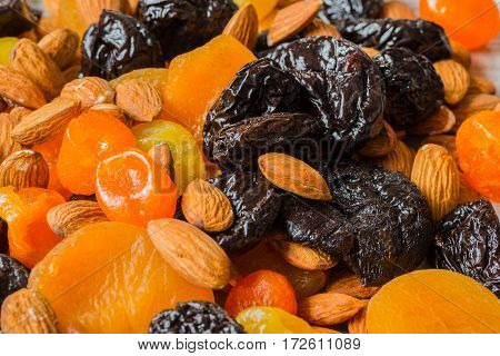 prunes, dried apricots, dried mandarins and almonds close-up.