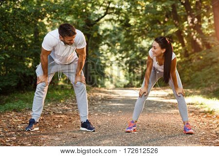 Young couple resting after running in the park