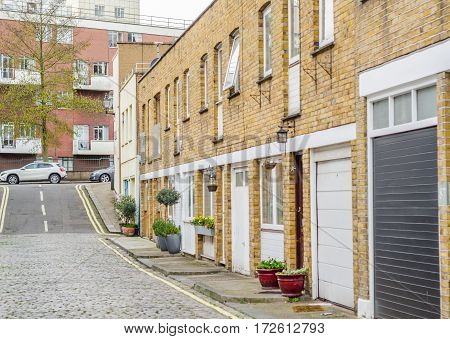 interesting street partially covered with paving stones low-rise buildings typical of the English quarter in the distance tall apartment building typical brick on the facade of the building urban architecture
