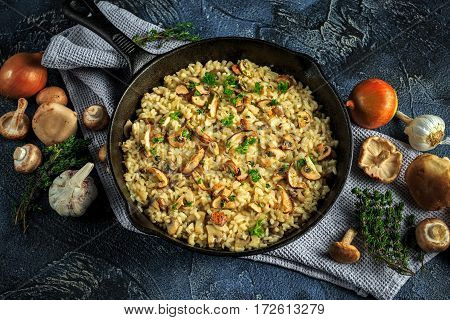 Mushroom Risotto in iron pan with herbs and parmesan cheese.