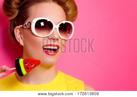 Portrait of stylish cute young blonde woman in sunglasses with colorful watermelon lollipop on pink background