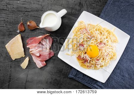 Pasta Carbonara. Spaghetti with bacon and parmesan cheese. Pasta Carbonara on white plate with parmesan on dark background.