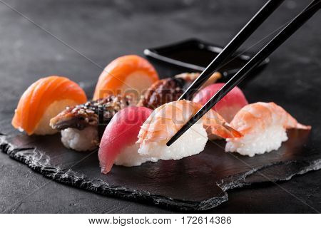 sashimi sushi with chopsticks and soy on black stone slate on dark background