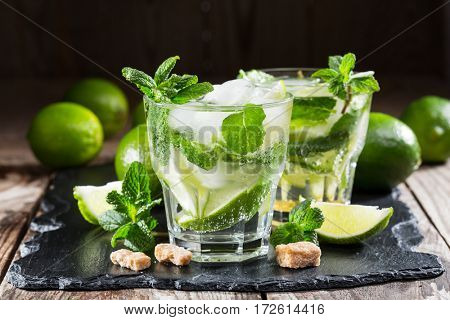 two glass of mojito cocktail with fresh lime and mint on a black stone board