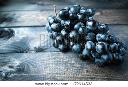 Bunch of black grapes on a shabby wooden background. Copy space