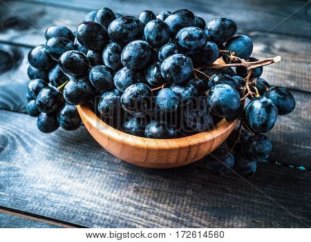 Bunch of black grapes in a bamboo bowl