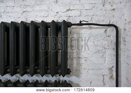 Old black cast iron radiator on a white brick wall