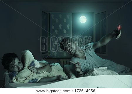 Older brother laugh down the scared and sleepless boy at bedroom in front of shiny moon