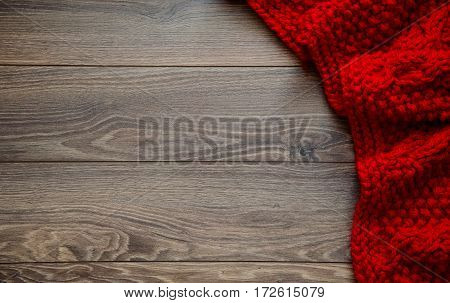 Knitted reddish blanket on a wooden background with copy space