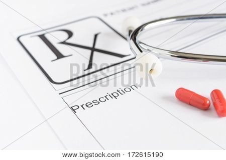 Medical prescription form with stethoscope and pills
