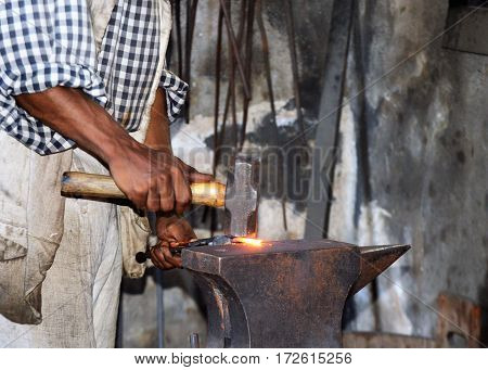 old colonial village blacksmith with hammer down