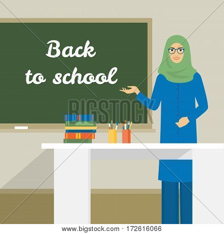 Arab woman stands near the board. The teacher in the classroom at the table. Back to school. Muslim girl wearing hijab