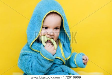 baby sitting with toy in blue robe