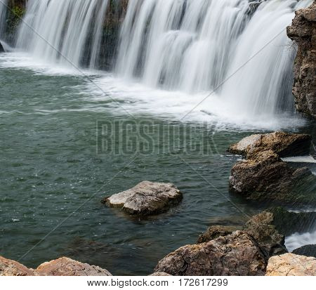 Waterfall among boulders on a warm winter day makes a scenic view