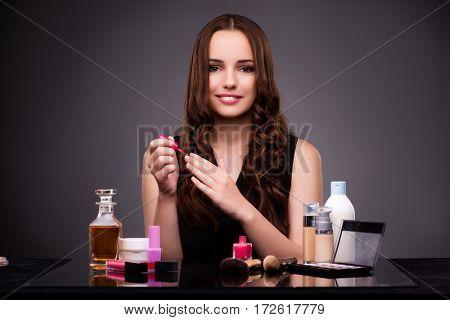 Woman doing makeup on dark background
