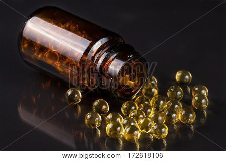 Fish oil capsules in a glass bottle isolated on white background.