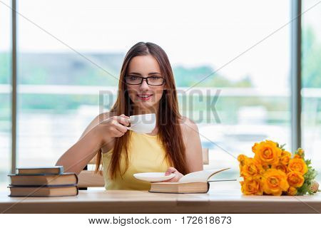 Young student drinking coffee while sudying