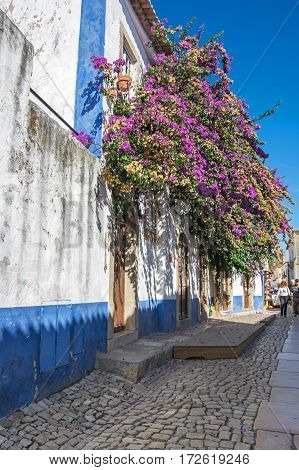 OBIDOS PORTUGAL - OCTOBER 15 2015: The street of Obidos in Portugal popular tourist destination because of its a well-preserved medieval architecture